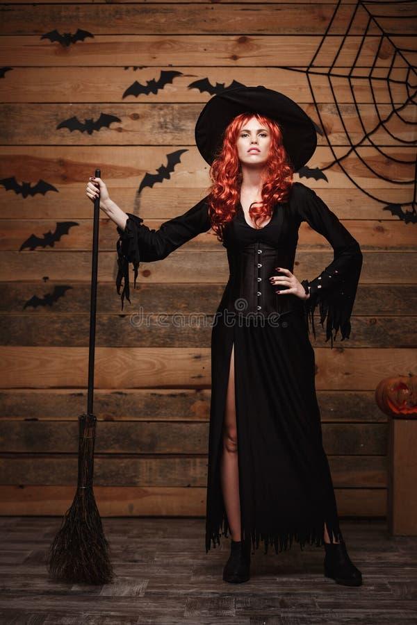 Concepto de la bruja de Halloween - bruja roja del pelo del feliz Halloween integral que celebra la presentación con el palo de e fotografía de archivo libre de regalías