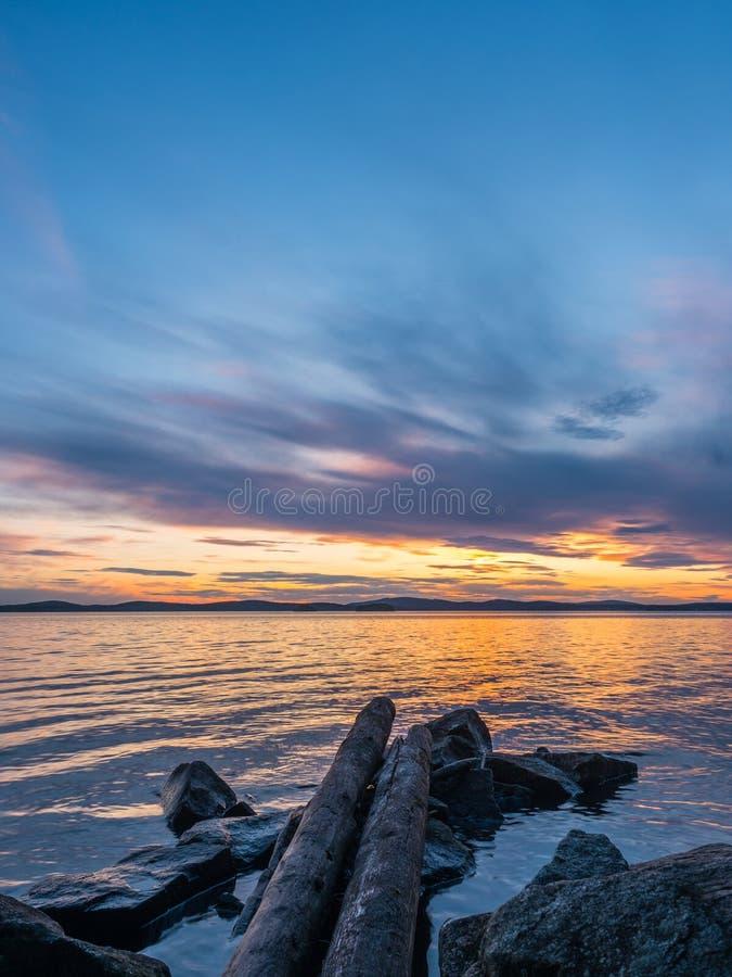 Concepto de la calma y de la meditaci?n Puesta del sol en el lago, las piedras y los árboles viejos en el primero plano, agua res fotografía de archivo libre de regalías