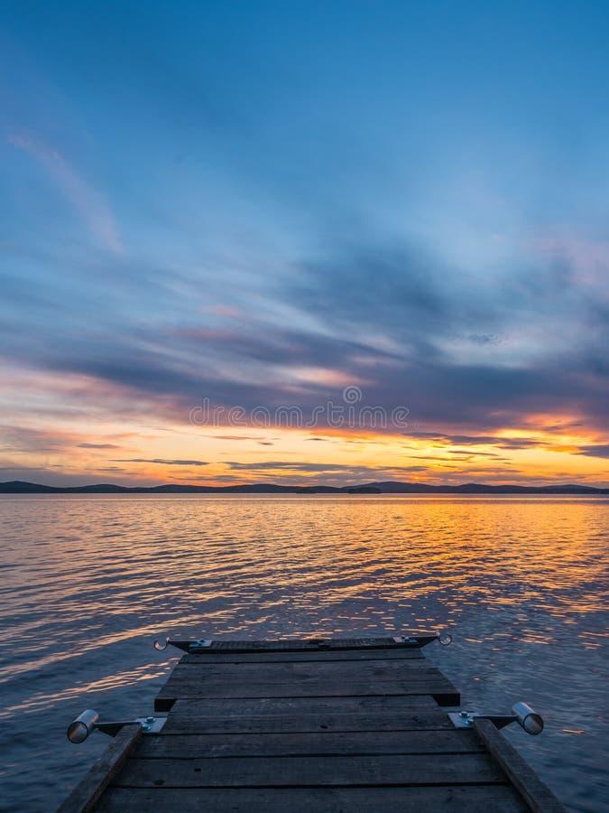 Concepto de la calma y de la meditaci?n Puesta del sol en el lago, puente de madera en el primero plano, agua reservada, cielo de imagenes de archivo