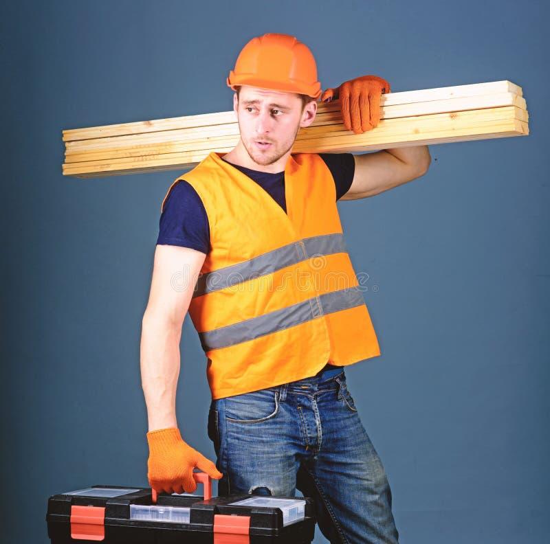 Concepto de la carpintería El carpintero, carpintero, trabajador, constructor en cara tranquila lleva haces de madera en hombro h imágenes de archivo libres de regalías