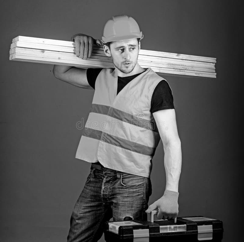 Concepto de la carpinter?a El carpintero, carpintero, trabajador, constructor en cara tranquila lleva haces de madera en hombro h imagen de archivo