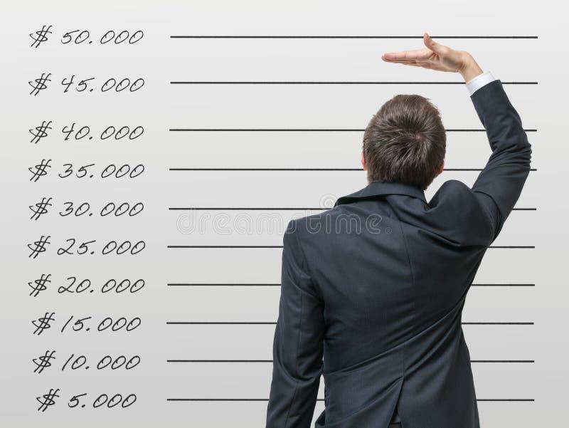 Concepto de la carrera El hombre está comparando su renta con el salario medio imagen de archivo