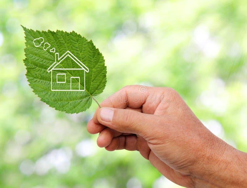 Concepto de la casa de Eco, mano que sostiene la casa del eco imagenes de archivo
