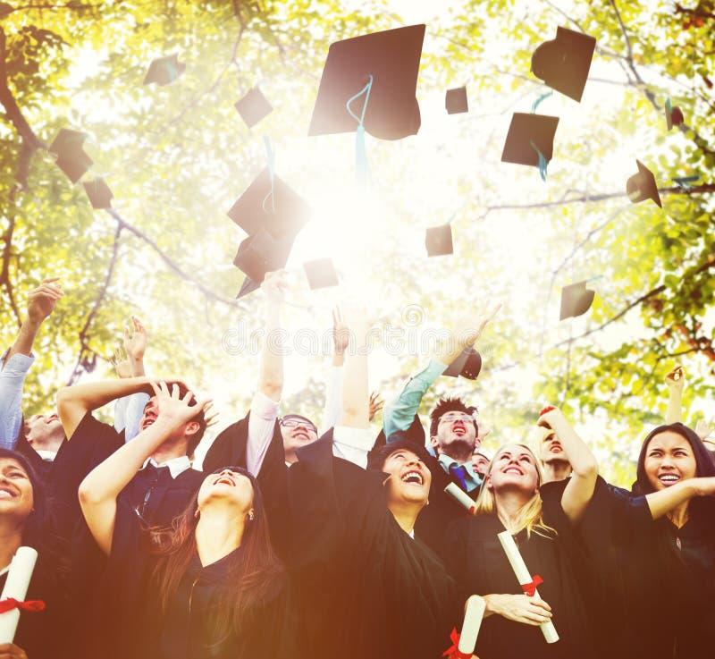 Concepto de la celebración del éxito de la graduación de los estudiantes de la diversidad imágenes de archivo libres de regalías
