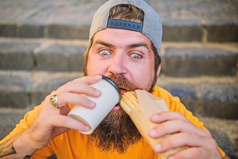 Concepto de la comida de la calle El hombre barbudo come la salchicha sabrosa Nutrici?n urbana de la forma de vida Junk Food Inco fotografía de archivo