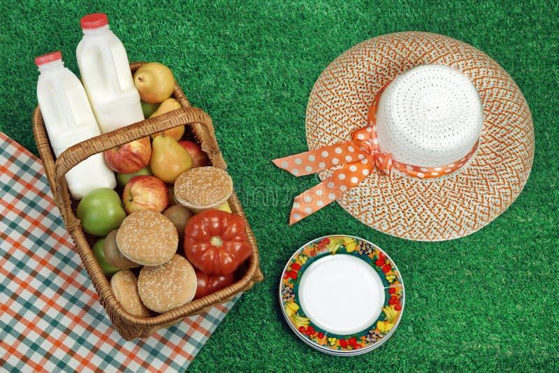 Concepto de la comida campestre del verano con Straw Hat And Food Basket fotografía de archivo