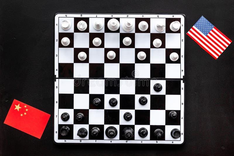 Concepto de la competencia del ajedrez Tablero de ajedrez con las figuras cerca de banderas americanas y chinas en la opinión sup imagen de archivo libre de regalías