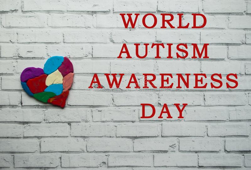 Concepto de la conciencia del autismo con el corazón de pedazos coloridos imagenes de archivo