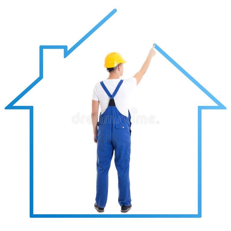 Concepto de la construcción - hombre en casa azul del dibujo del uniforme del constructor fotos de archivo libres de regalías