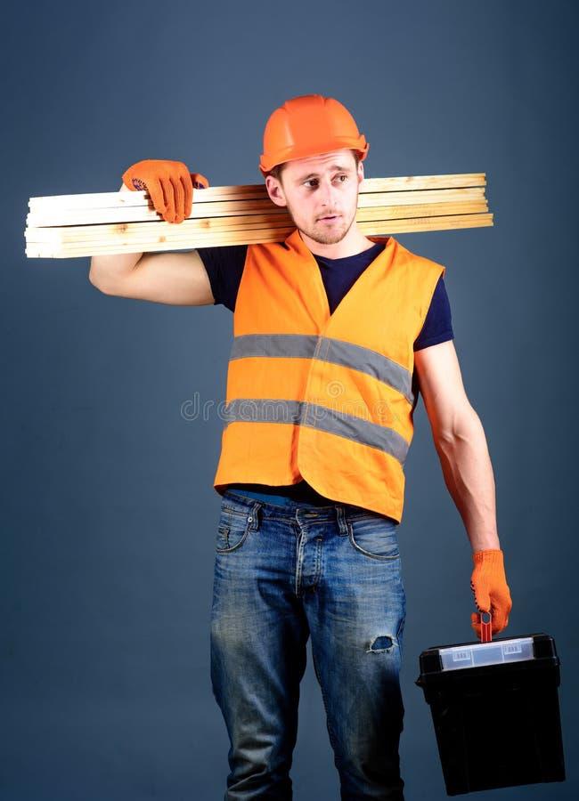 Concepto de la construcción y de la carpintería El carpintero, carpintero, trabajador, constructor en cara soñadora lleva haces d fotografía de archivo