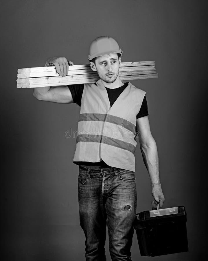 Concepto de la construcción y de la carpintería El hombre en el casco, casco lleva a cabo la caja de herramientas y los haces de  fotografía de archivo libre de regalías