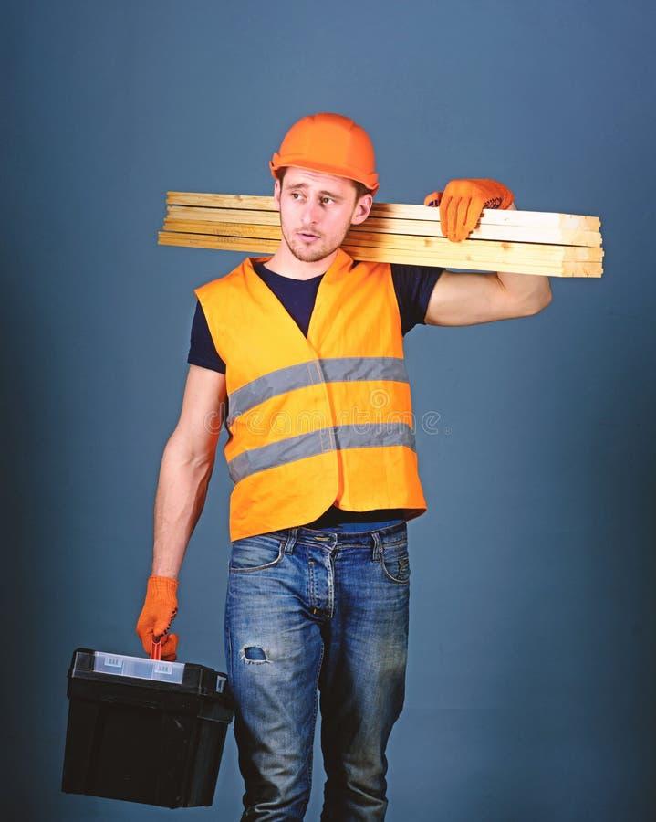 Concepto de la construcción y de la carpintería El hombre en el casco, casco lleva a cabo la caja de herramientas y los haces de  fotos de archivo