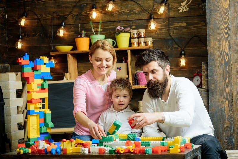 Concepto de la cooperación Los miembros de la familia cooperan en el modelo de estructura de edificio, cooperación Cooperación y  imagen de archivo