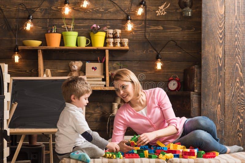 Concepto de la cooperación La madre y el hijo cooperan en el modelo de estructura de edificio, cooperación Cooperación y cooperat imagen de archivo