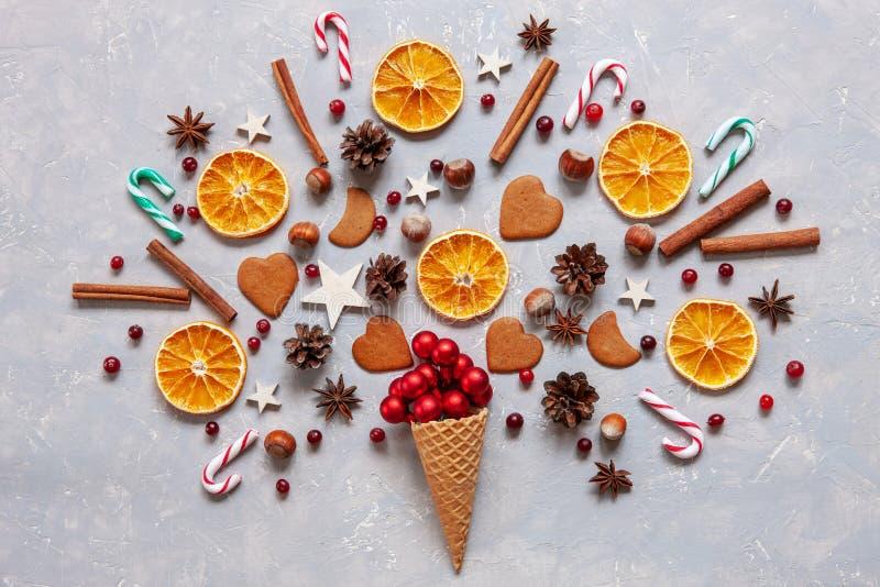Concepto de la creatividad de la Navidad con las bolas rojas, bastones de caramelo, galletas, especias, rebanadas anaranjadas sec fotografía de archivo libre de regalías