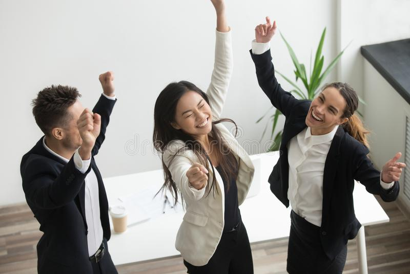 Concepto de la danza de la victoria, compañeros de trabajo diversos emocionados que celebran el autobús imagenes de archivo