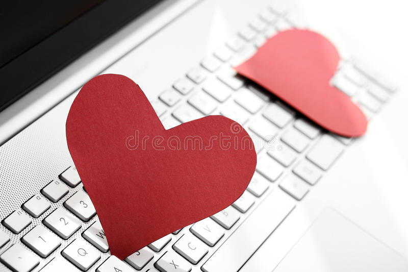 Concepto de la datación de Internet - dos corazones de papel en el teclado de ordenador fotografía de archivo libre de regalías