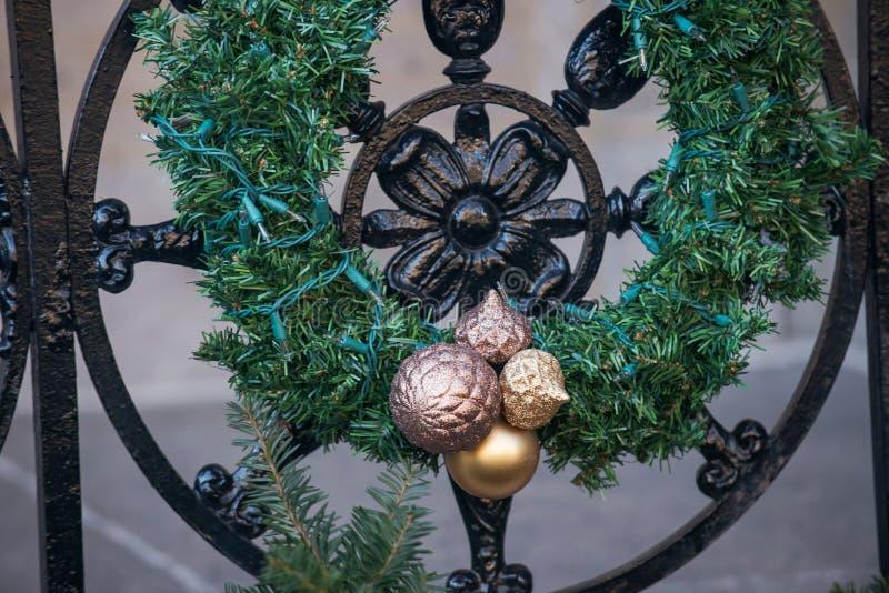 Concepto de la decoración de las vacaciones de invierno del aire libre: Guirnalda natural de la Navidad con las bolas coloridas q fotografía de archivo