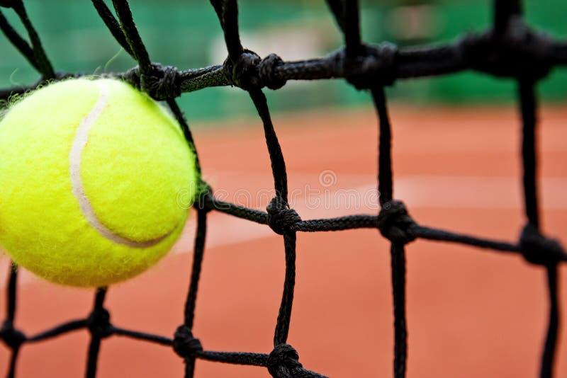 Concepto de la derrota del incidente - pelota de tenis en la red imagen de archivo libre de regalías
