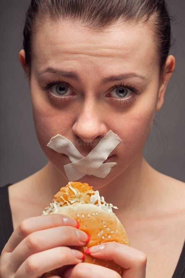 Concepto de la dieta: mujer que sostiene una hamburguesa con la boca sellada imagenes de archivo