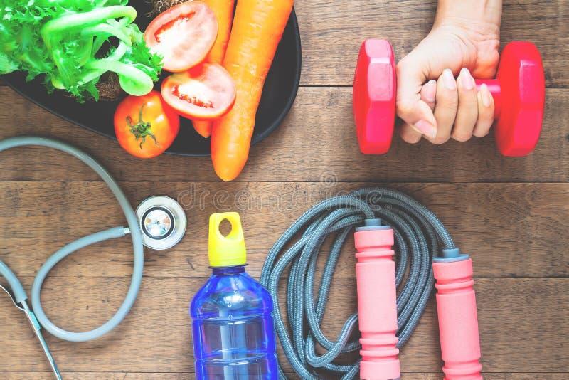 Concepto de la dieta y de la aptitud Pesa de gimnasia de la tenencia de la mano de la mujer, comidas sanas y equipos de la aptitu foto de archivo libre de regalías