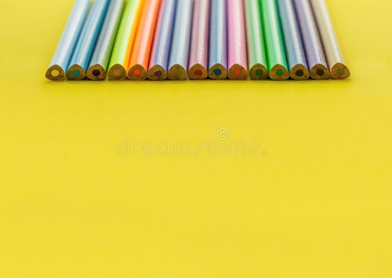 Concepto de la diversidad fila del lápiz del color de la mezcla en fondo amarillo imagen de archivo libre de regalías