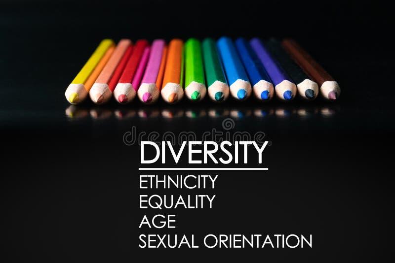 Concepto de la diversidad fila del lápiz del color de la mezcla en fondo negro con la diversidad del texto, pertenencia étnica, i foto de archivo
