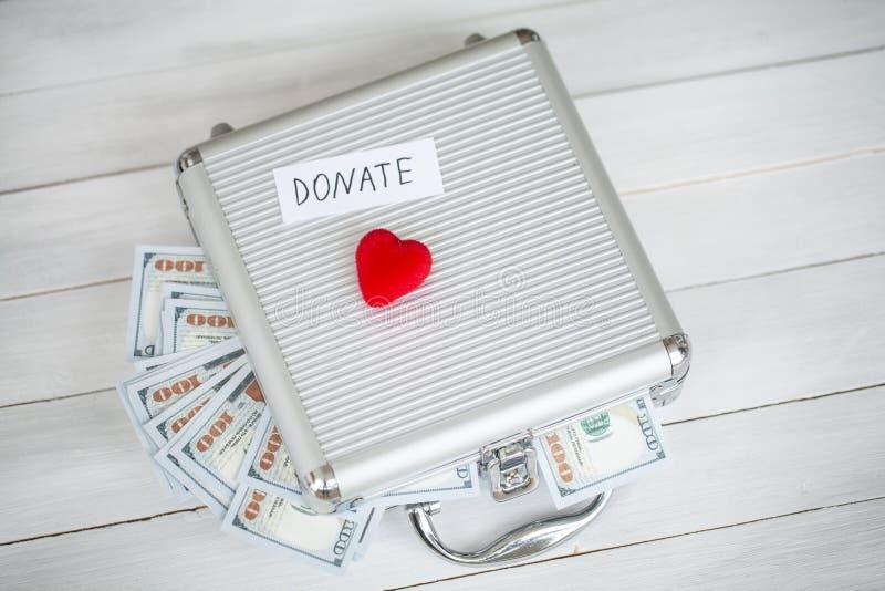 Concepto de la donación Caso con los dólares en el fondo blanco donaciones De alta resolución foto de archivo