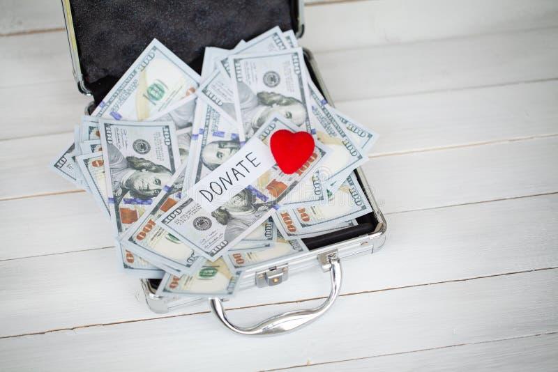 Concepto de la donación Caso con los dólares en el fondo blanco donaciones De alta resolución imágenes de archivo libres de regalías