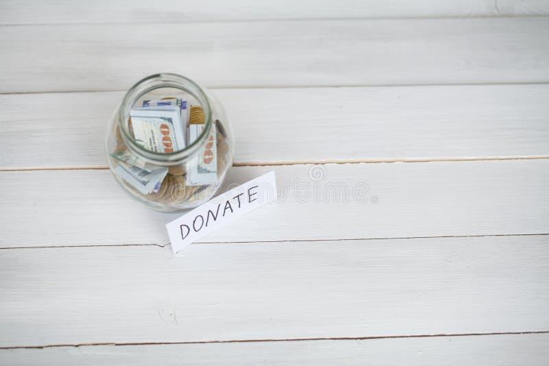 Concepto de la donación Vidrio con los dólares en el fondo blanco donaciones imagen de archivo libre de regalías