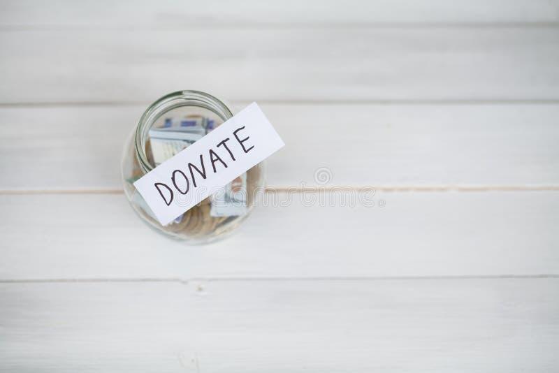 Concepto de la donación Vidrio con los dólares en el fondo blanco donaciones imagen de archivo
