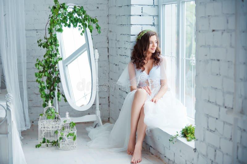 Concepto de la dulzura y de la sensualidad Modelo moreno hermoso que presenta en cama en la ropa interior blanca Retrato sensual  imagen de archivo