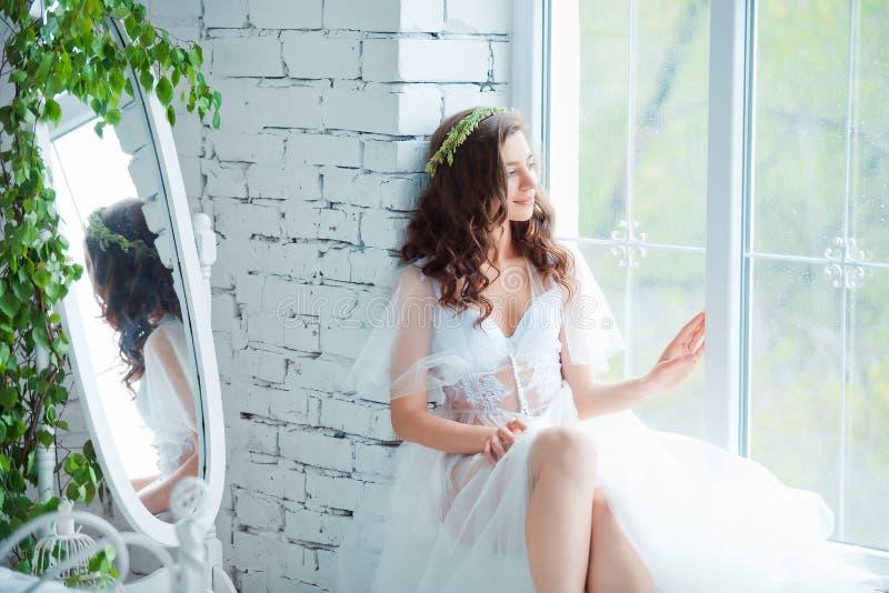 Concepto de la dulzura y de la sensualidad Modelo moreno hermoso que presenta en cama en la ropa interior blanca Retrato sensual  fotos de archivo