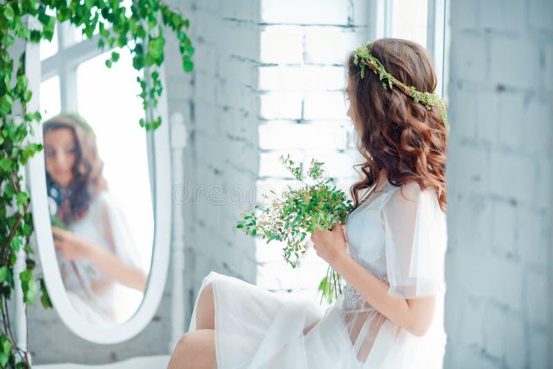 Concepto de la dulzura y de la sensualidad Modelo moreno hermoso que presenta en cama en la ropa interior blanca Retrato sensual  imágenes de archivo libres de regalías