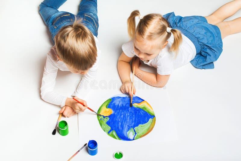 Concepto de la ecolog?a con dos ni?os prety que pintan la tierra en el fondo blanco imagen de archivo libre de regalías