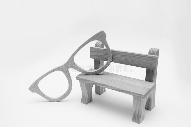 Concepto de la edad avanzada, banco modelo de madera con los vidrios de madera en a foto de archivo