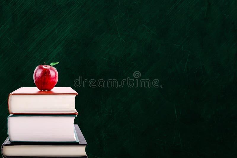 Concepto de la educación con Apple en los libros y el fondo de la pizarra fotos de archivo libres de regalías