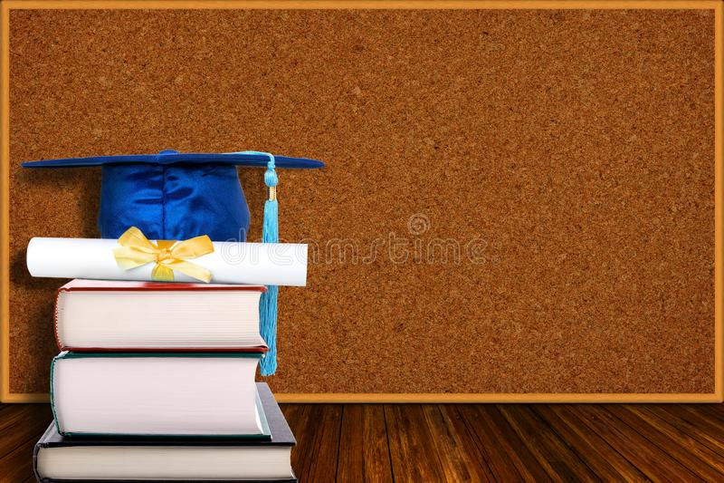Concepto de la educación con el sombrero y el diploma de la graduación en fondo del tablero de los libros y del corcho fotografía de archivo