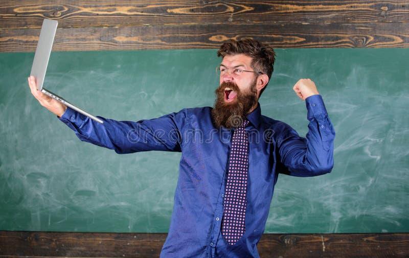 Concepto de la educación a distancia El hombre barbudo del profesor con el ordenador portátil moderno pasó prueba el fondo en lín imagen de archivo libre de regalías