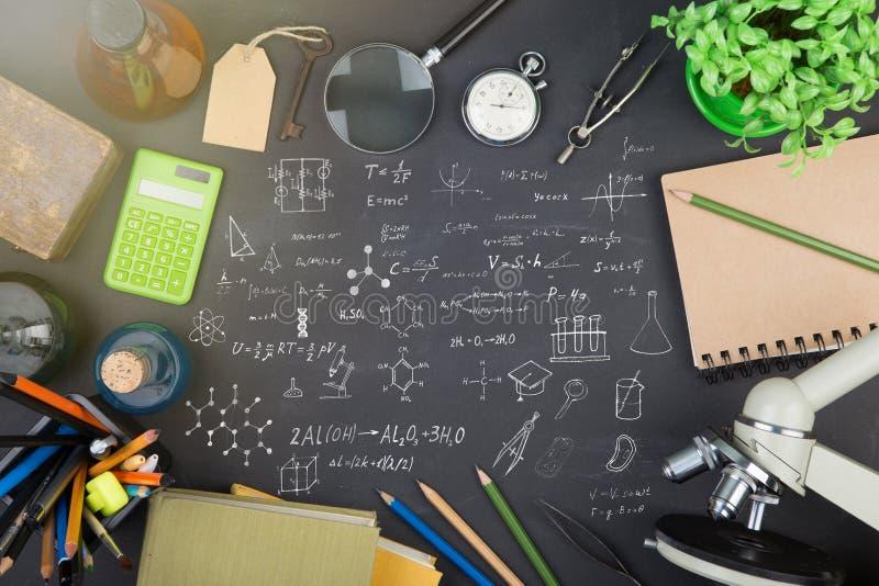 Concepto de la educación - libros, microscopio y bosquejo de la ciencia en la pizarra imagen de archivo libre de regalías