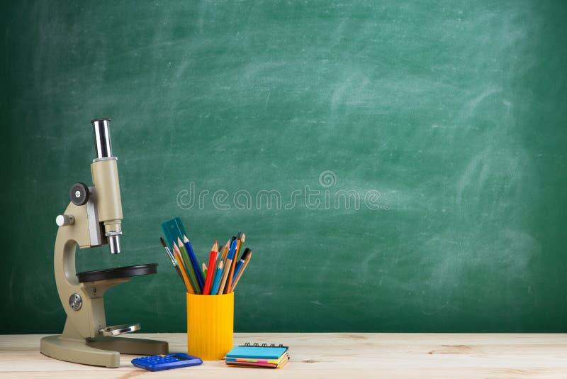 Concepto de la educación - microscopio en el escritorio en el auditorio, fondo de la pizarra foto de archivo libre de regalías
