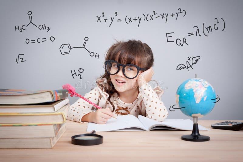 Concepto de la educación, niña linda en la escuela feliz a hacer h fotografía de archivo libre de regalías