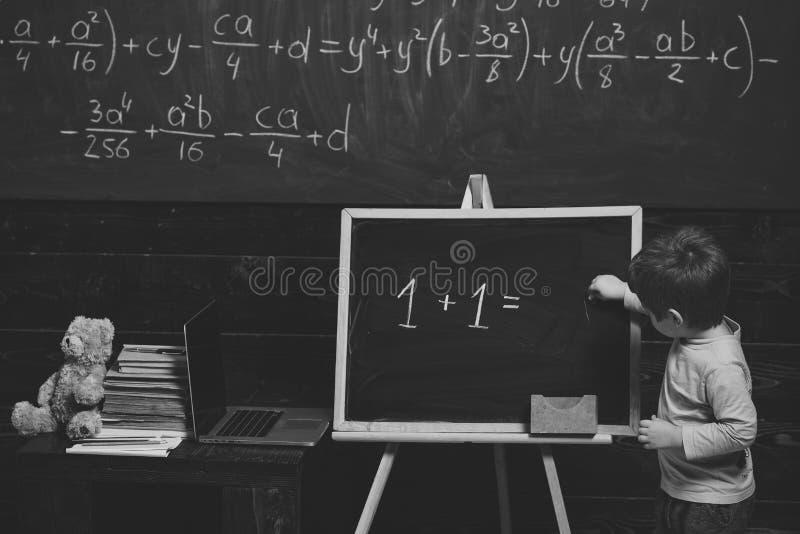 Concepto de la educación Niño pequeño que soluciona la ecuación en la pizarra Entrenamiento preescolar para el niño elegante fotografía de archivo