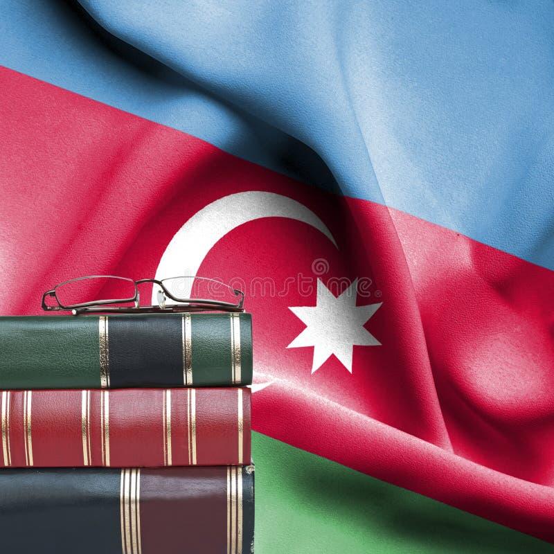 Concepto de la educación - pila de libros y de vidrios de lectura contra la bandera nacional de Azerbaijan imagen de archivo