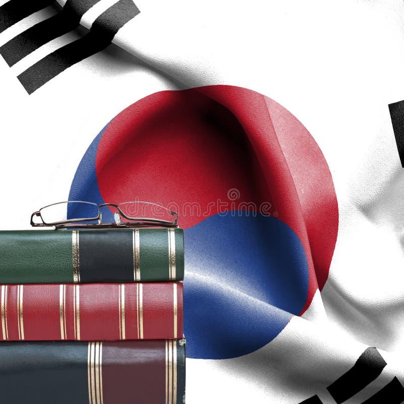 Concepto de la educación - pila de libros y de vidrios de lectura contra la bandera nacional de la Corea del Sur fotos de archivo libres de regalías