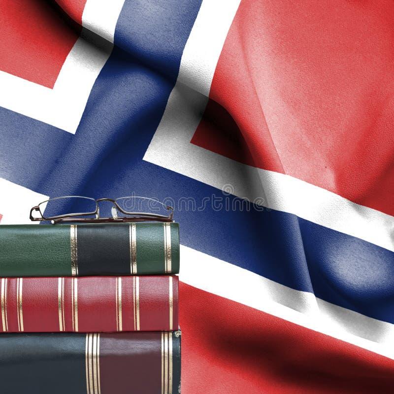 Concepto de la educación - pila de libros y de vidrios de lectura contra la bandera nacional de Noruega imagenes de archivo