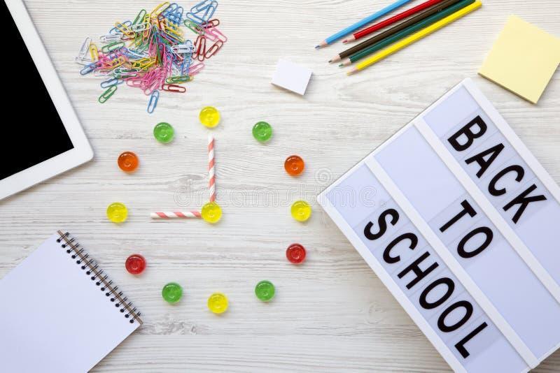 Concepto de la educación Reloj del ` de nueve o en el reloj Reloj hecho de caramelos coloridos, ` de nuevo a palabra del ` de la  imágenes de archivo libres de regalías