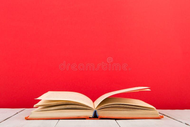 concepto de la educación y de la sabiduría - libro abierto en la tabla de madera, fondo del color imágenes de archivo libres de regalías