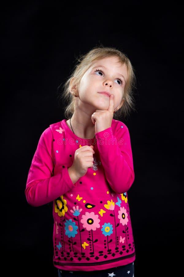 Concepto de la emoción: niña adorable soñadora Fondo negro, foto del estudio imagenes de archivo
