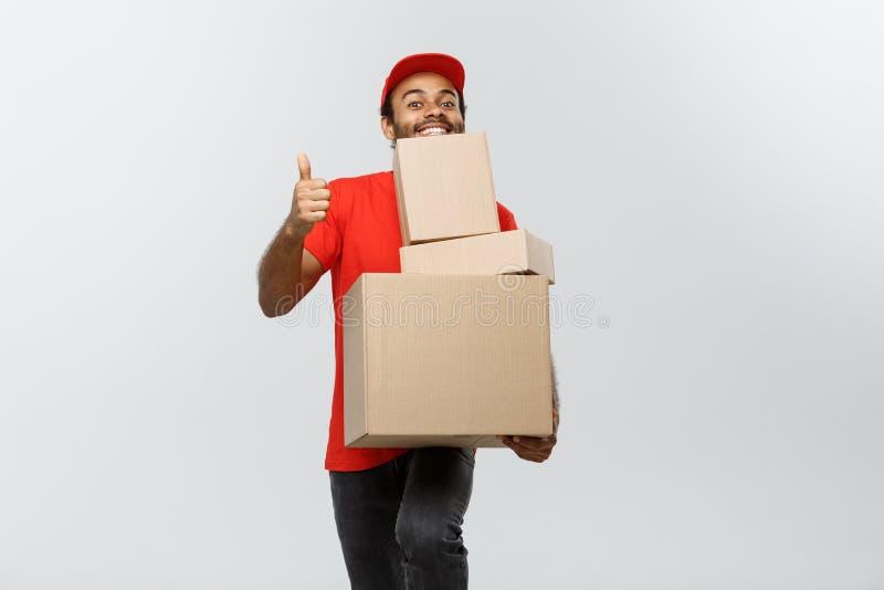 Concepto de la entrega - el retrato del hombre de entrega afroamericano feliz que lleva a cabo los paquetes de la caja y que mues fotos de archivo libres de regalías